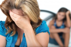 Sad and worried mother with her troubled teenage daughter in the